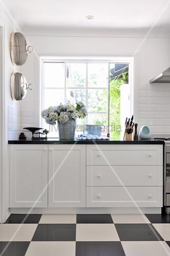 Küchenzeile unter Fenster und schwarz weisser Schachbrettboden in Landhausküche u2013 Bild kaufen