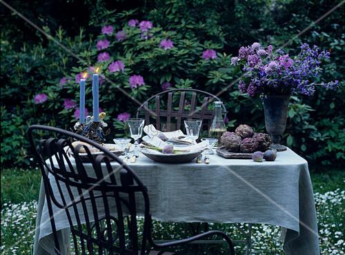 romantisch gedeckter tisch mit kerzen und blumen im garten. Black Bedroom Furniture Sets. Home Design Ideas