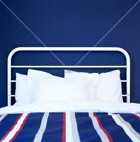 bett mit weiss lackiertem metallgestell vor dunkelblauer wand bild kaufen living4media. Black Bedroom Furniture Sets. Home Design Ideas