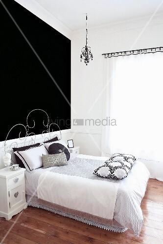 bett mit filigranem metallgestell vor schwarz get nter wand in modernem schlafzimmer bild. Black Bedroom Furniture Sets. Home Design Ideas