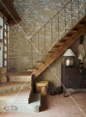 holztreppe vor natursteinwand im vorraum eines rustikos. Black Bedroom Furniture Sets. Home Design Ideas