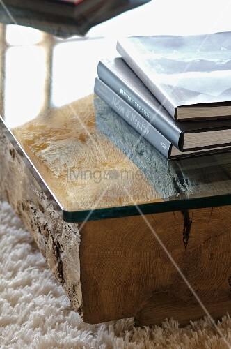 Bücherstapel auf bodennahem Tisch mit Glasplatte auf Holzstamm ...