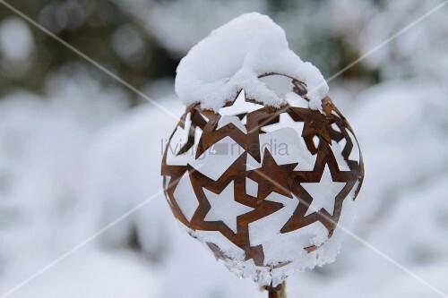 sternekugel aus rost mit schnee bedeckt bild kaufen living4media. Black Bedroom Furniture Sets. Home Design Ideas