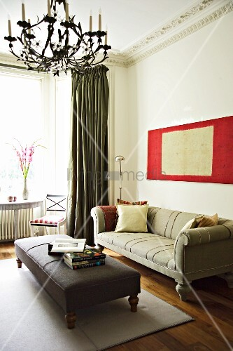 Gepolsterter Couchtisch vor antikem Sofa in klassisc