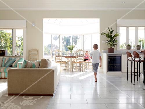kleiner junge l uft durch den offenen wohnraum mit sonnigem essbereich bild kaufen living4media. Black Bedroom Furniture Sets. Home Design Ideas