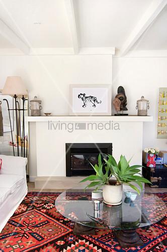 runder glastisch auf bunt gemustertem teppich vor dem kamin in einem wohnzimmer bild kaufen. Black Bedroom Furniture Sets. Home Design Ideas