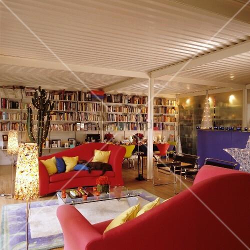 Rote sofas und eine volle b cherwand in weihnachtlich dekorierter loftwohnung mit Hundeurin aus sofa entfernen