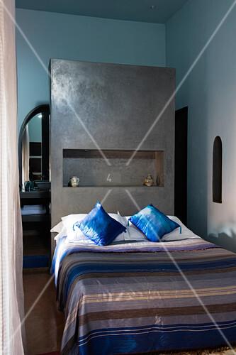 Marokkanisches schlafzimmer mit gestreifter tagesdecke auf bett vor grau get ntem raumteiler - Tagesdecke schlafzimmer ...