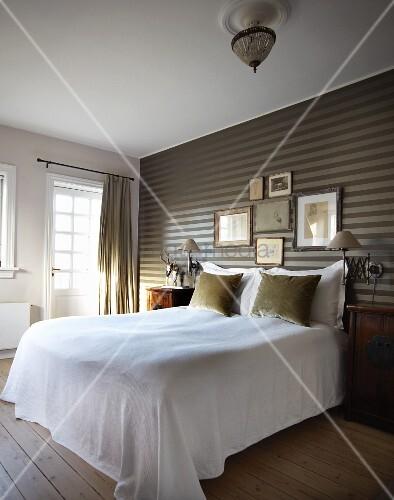 elegantes schlafzimmer bett mit weissem berwurf vor gestreifter tapete an wand bild kaufen. Black Bedroom Furniture Sets. Home Design Ideas