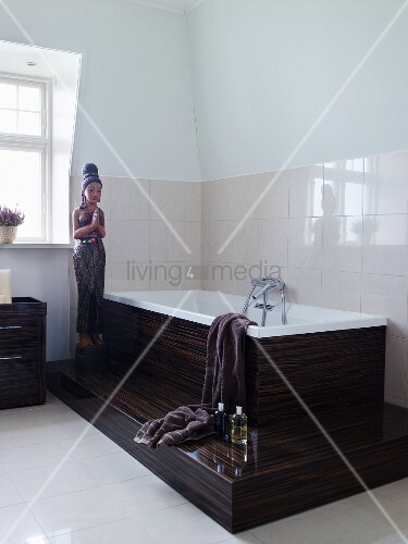 statue auf podest neben badewanne mit tropischer holzverkleidung und weissen fliesen an wand. Black Bedroom Furniture Sets. Home Design Ideas