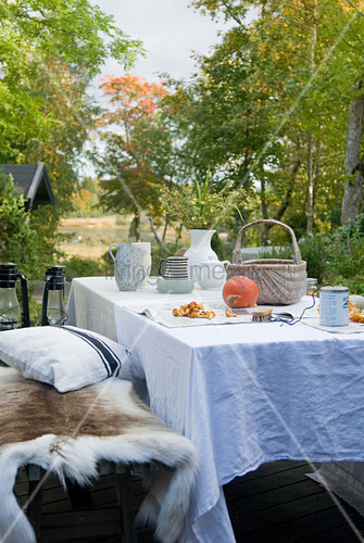herbstlicher tisch mit weisser tischdecke und bank mit tierfell im freien bild kaufen. Black Bedroom Furniture Sets. Home Design Ideas