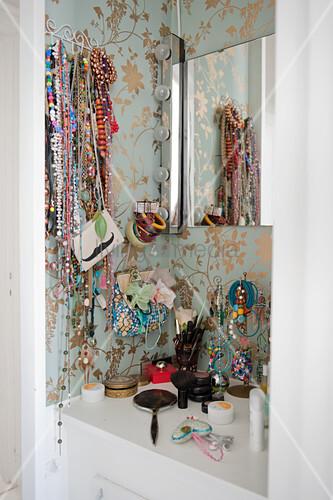 offene schmuckaufbewahrung ber schminktisch an tapezierter wand mit goldenem blumenmuster in. Black Bedroom Furniture Sets. Home Design Ideas