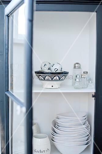 offener schrank mit glast r und blick auf weisses geschirr. Black Bedroom Furniture Sets. Home Design Ideas