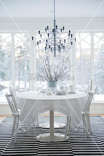 designer h ngeleuchte ber esstisch und st hle in weiss auf teppich mit schwarz weissen streifen. Black Bedroom Furniture Sets. Home Design Ideas