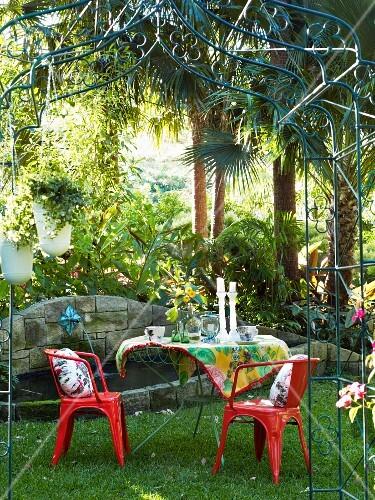 gartentisch mit roten st hlen unter rosenbogen aus metall im hintergrund steinbrunnen bild. Black Bedroom Furniture Sets. Home Design Ideas