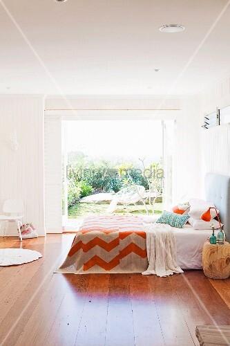 schlafzimmer mit dielenboden doppelbett vor weit ge ffneten terrassent ren bild kaufen. Black Bedroom Furniture Sets. Home Design Ideas