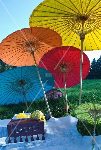 bunte schirme mit bambusstiel spenden schatten auf der picknickdecke bild kaufen living4media. Black Bedroom Furniture Sets. Home Design Ideas