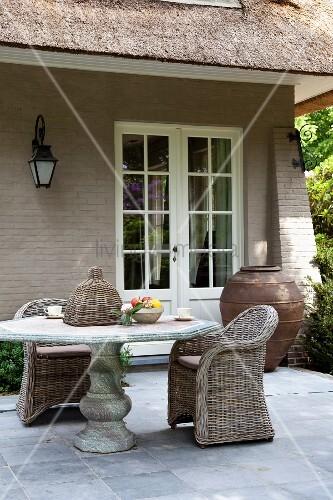 Steintisch und korbst hle auf terrasse vor landhaus bild for Innendesigner schweiz