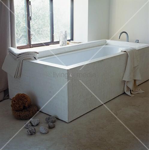 designer badewanne vor fenster und steine auf betonfussboden bild kaufen living4media. Black Bedroom Furniture Sets. Home Design Ideas