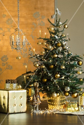 gold geschm ckter weihnachtsbaum mit lichterkette davor goldfarbener w rfel hocker bild. Black Bedroom Furniture Sets. Home Design Ideas
