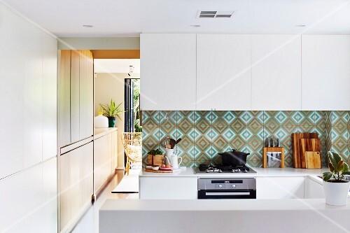 spritzschutz mit gemusterten wandfliesen in weisser offener k che bild kaufen living4media. Black Bedroom Furniture Sets. Home Design Ideas