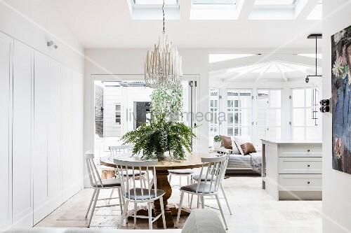 essplatz mit weissen st hlen um runden holztisch in offenem wohnraum im hintergrund k chentheke. Black Bedroom Furniture Sets. Home Design Ideas