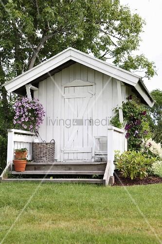 weisses gartenh uschen aus holz mit kleiner veranda und blumenampel bild kaufen living4media. Black Bedroom Furniture Sets. Home Design Ideas