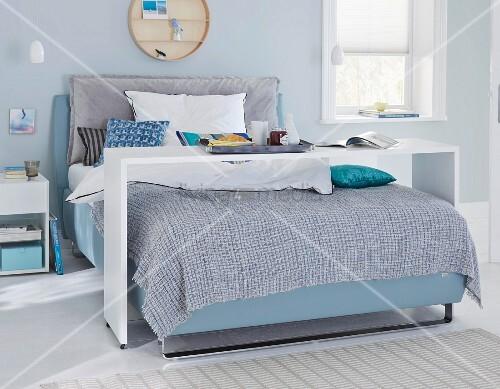 boxspringbett mit bettbr cke im schlafzimmer in blauen t nen bild kaufen living4media. Black Bedroom Furniture Sets. Home Design Ideas