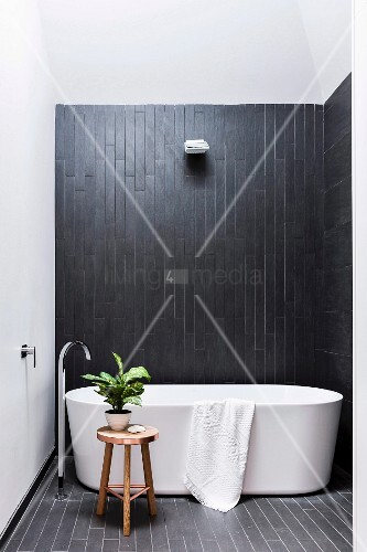 freistehende badewanne mit standarmatur vor schwarzer. Black Bedroom Furniture Sets. Home Design Ideas