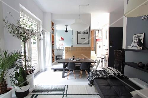 modernes wohnzimmer mit tagesbett und pflanzen auf podest im hintergrund essbereich mit. Black Bedroom Furniture Sets. Home Design Ideas