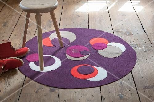 runder violetter teppich aus walkstoff mit aufgen hten unterschiedlichen kontrastfarbigen. Black Bedroom Furniture Sets. Home Design Ideas