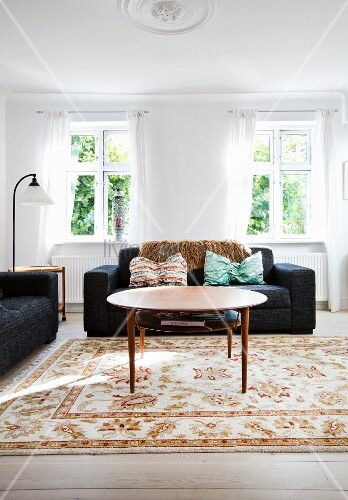 runder couchtisch und schwarzes sofa im hellen wohnzimmer. Black Bedroom Furniture Sets. Home Design Ideas