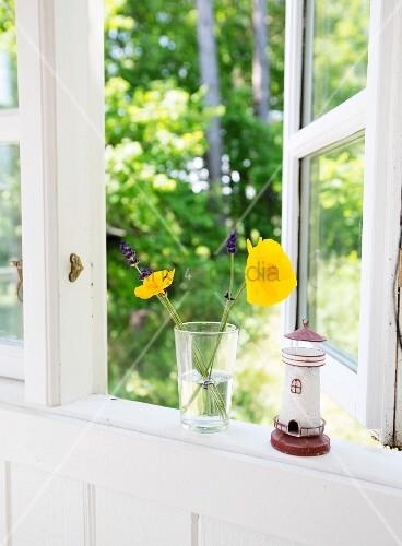 blumen im glas und leuchtturm am fenster mit blick in den garten bild kaufen living4media. Black Bedroom Furniture Sets. Home Design Ideas