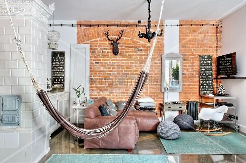 h ngematte im wohnzimmer mit betonwand und kachelofen bild kaufen living4media. Black Bedroom Furniture Sets. Home Design Ideas