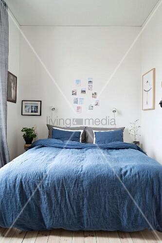 schmales schlafzimmer mit blauer bettw sche auf doppelbett und verschiedenen fotos als. Black Bedroom Furniture Sets. Home Design Ideas