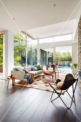 modernes wohnzimmer mit fensterfront zum garten bild kaufen living4media. Black Bedroom Furniture Sets. Home Design Ideas