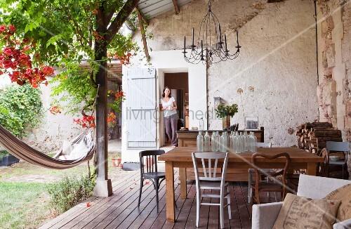 Berdachte landhaus terrasse mit holztisch und glasflaschensammlung frau in t r ffnung stehend - Holztisch terrasse ...