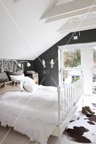 doppelbett mit weisser tagesdecke und kuhfellteppich im dachzimmer bild kaufen living4media. Black Bedroom Furniture Sets. Home Design Ideas