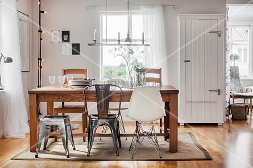 verschiedene st hle um einen holztisch im hellen esszimmer bild kaufen living4media. Black Bedroom Furniture Sets. Home Design Ideas