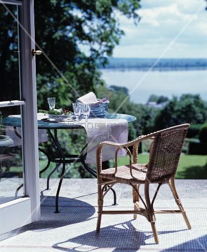 korbstuhl und runder tisch auf der terrasse mit blick auf. Black Bedroom Furniture Sets. Home Design Ideas