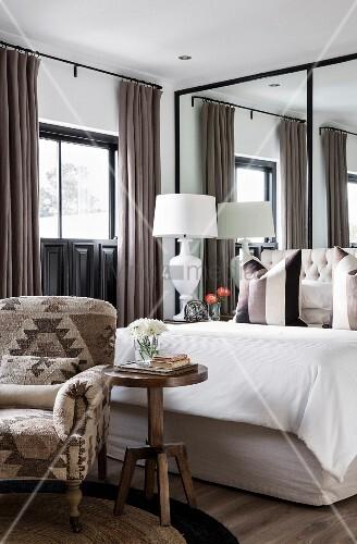 elegantes schlafzimmer in erdt nen mit spiegelwand hinter. Black Bedroom Furniture Sets. Home Design Ideas