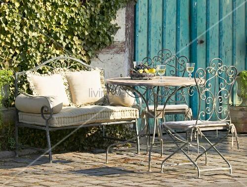 romantische gartenm bel aus metall vor begr nter traditioneller fachwerkwand bild kaufen. Black Bedroom Furniture Sets. Home Design Ideas