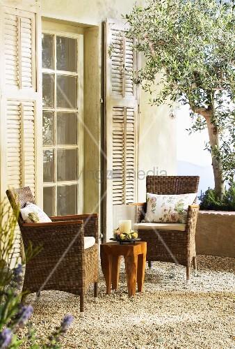 zwei korbst hle und ein holztisch auf mediterraner. Black Bedroom Furniture Sets. Home Design Ideas