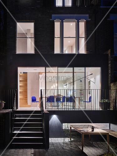 blick von der terrasse ins beleuchtete haus mit essbereich im erdgeschoss bild kaufen. Black Bedroom Furniture Sets. Home Design Ideas