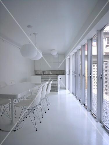 Weisser Essbereich mit langer Tisch und Klassikerstühlen ...