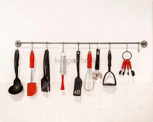 schwarze und rote k chenutensilien an einer hakenleiste bild kaufen living4media. Black Bedroom Furniture Sets. Home Design Ideas