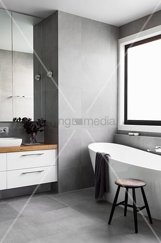 frei stehende badewanne vor fenster und waschtisch in grau. Black Bedroom Furniture Sets. Home Design Ideas