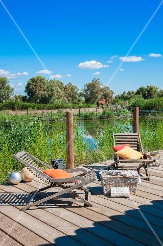 zwei liegest hle auf einer terrasse am sommerlichen see bild kaufen living4media. Black Bedroom Furniture Sets. Home Design Ideas