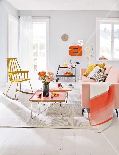 wohnzimmer mit zartrosa sofa tabletttisch und gelbem schaukelstuhl bild kaufen living4media. Black Bedroom Furniture Sets. Home Design Ideas
