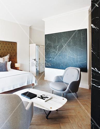 graue sessel und couchtisch vor dem bett im schlafzimmer bild kaufen living4media. Black Bedroom Furniture Sets. Home Design Ideas